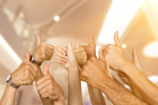 Happy people in a minibus or coach put their thumbs up.